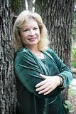 Mature Blond Leans on Tree