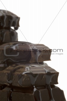 liquid and black bitter chocolate on white background