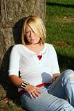 Blond Woman Sitting On Ground By Tree