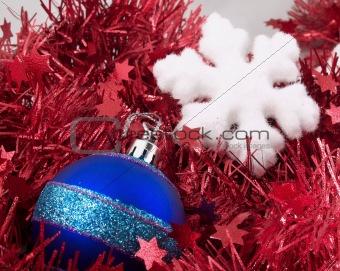 Christmas ball and snowflake on red tinsel