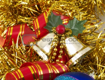 Christmas bells and ribbon on gold tinsel
