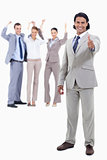 Businessman smiling with his thumbs up and cheering people behin