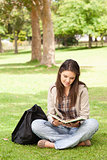Teenager sitting while reading a textbook