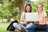 Smiling teenagers sitting while using a laptop