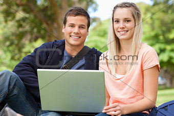 Portrait of two students laughing while sitting with a laptop