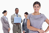 Woman with hands on her hips with business team in the backgroun