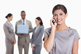 Woman with her head tilted slightly smiling on the phone and co-