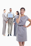 Businesswoman on the phone with a hand on her hip with co-worker