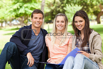 Portrait of three teenagers studying together
