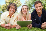 Three smiling students using a tactile tablet