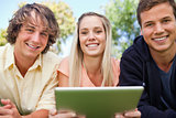 Portrait of three students using a tactile tablet