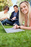 Close-up of a girl using a laptop while lying in a park