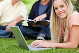 Portrait of a smiling girl using a laptop while lying in a park