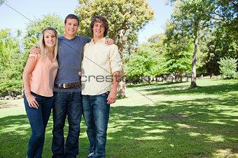 Portrait of three smiling students shoulder to shoulder