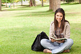 Smiling teenager sitting while holding a textbook