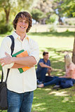 Smiling young man posing with textbook
