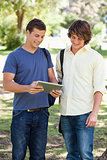 Two smiling male students with a touch pad