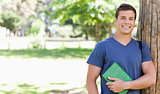 Portrait of a smiling muscled student holding a textbook