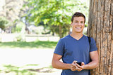 Portrait of a muscled young man with a smartphone