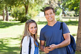 Portrait of a student showing his smartphone screen to a girl