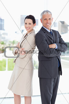 Smiling business people looking at the camera while standing upr