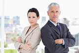 Business people standing upright in front of the window side by