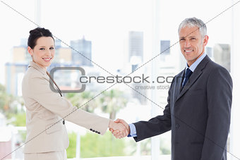 Smiling business people shaking hands while looking at the camer