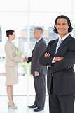 Young businessman standing upright in front of colleagues shakin