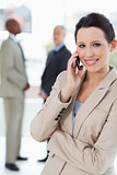 Smiling businesswoman talking on the cell phone while crossing h