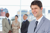 Smiling businessman standing upright with his team between him