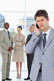 Serious businessman using a cell phone while his team is behind