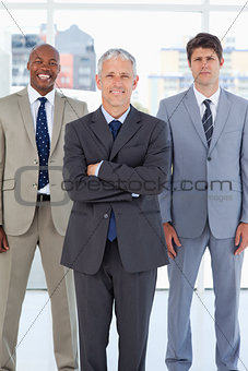 Mature director standing in front of a relaxed co-worker and a s