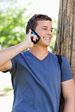 Close-up of a smiling young man on the phone