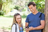 Close-up of a student showing his smartphone screen to a girl