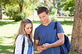 Close-up of a student showing his smartphone to a girl