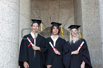Portrait of graduates holding their diploma