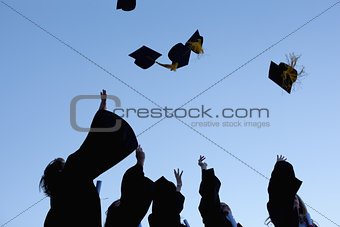Five graduates throwing their hats in the sky