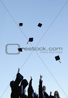 Five grad students throwing their hats high in the sky