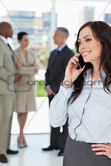 Young executive woman talking on the phone with one hand on her