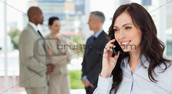 Businesswoman talking on the phone in a relaxed way with her tea