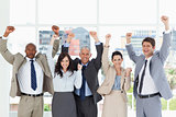 Smiling business team standing upright with arms raised in succe