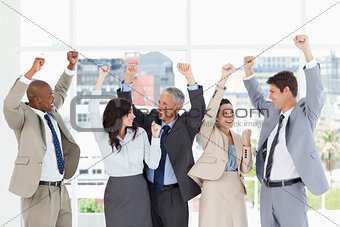 Five business people looking at each other and raising their arm