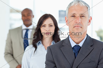 Mature and serious manager standing upright and followed by two