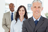 Three smiling business people standing upright and looking ahead