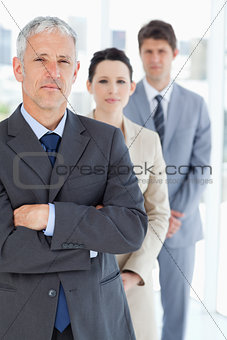 Serious manager crossing his arms in front of his business team