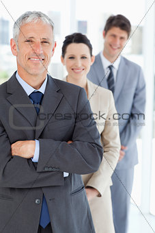 Smiling mature businessman standing upright in front of his youn