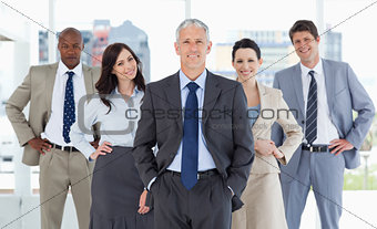 Business team smiling and standing upright with their hands on t