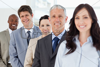 Three smiling business people in the background following their