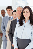 Serious executive woman standing upright in front of her busines