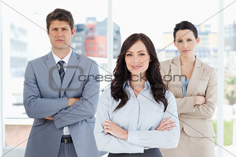 Three business people crossing their arms in front of a bright w